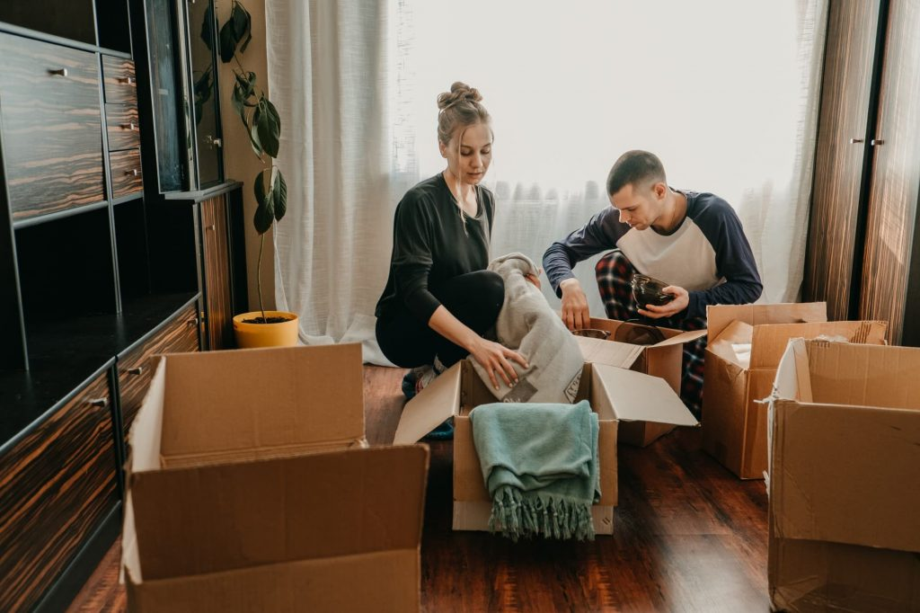 couple moving boxes from apartment