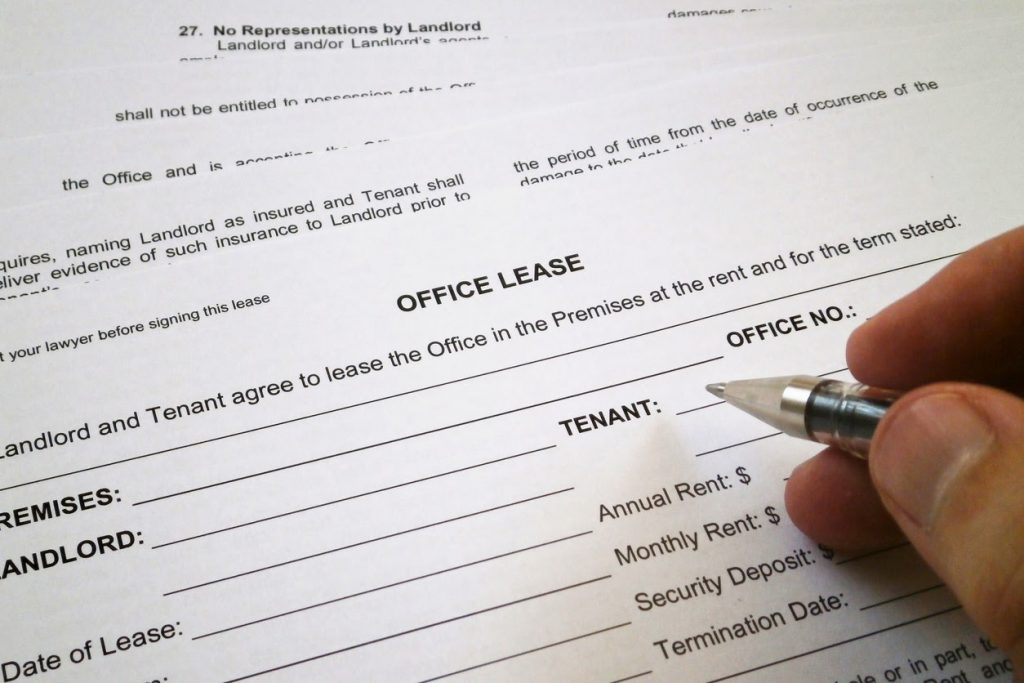 Close-up shot of a hand filling out a rental agreement for subletting office space.