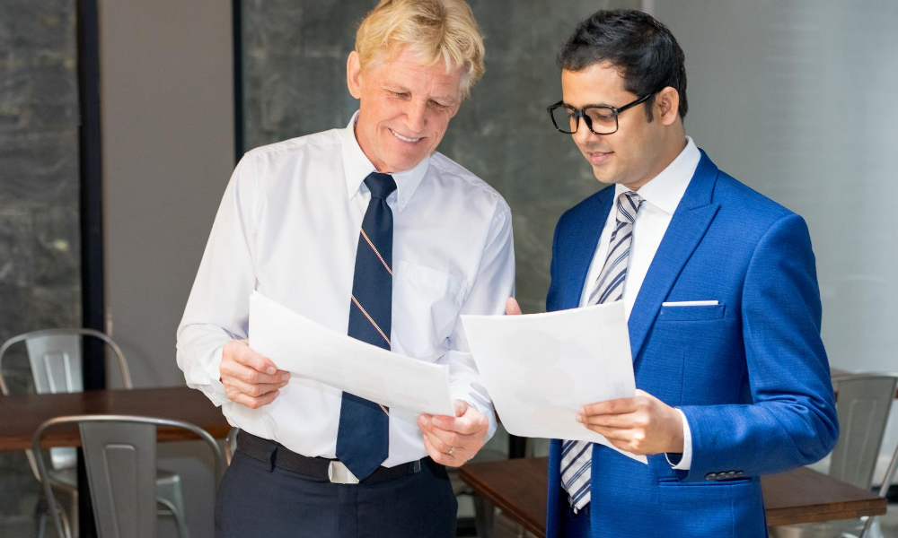 Two businessmen reviewing the contract that reviews a commercial lease audit.