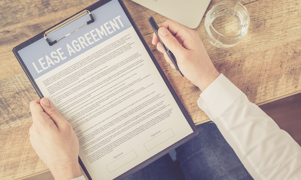 Man signing an agreement after looking through the commercial lease insurance clauses.