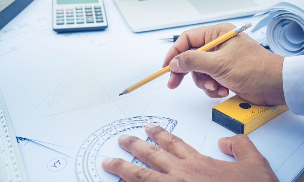 A designer uses drafting tools to draw up a CRE office design that fits the project budget.
