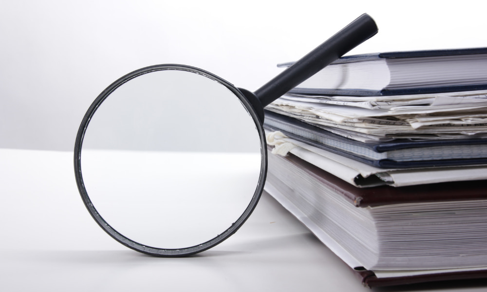 magnifying glass over a stack of documents