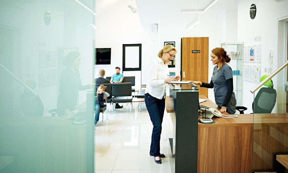 two women standing at a desk while showing off the dental office design and furniture selection
