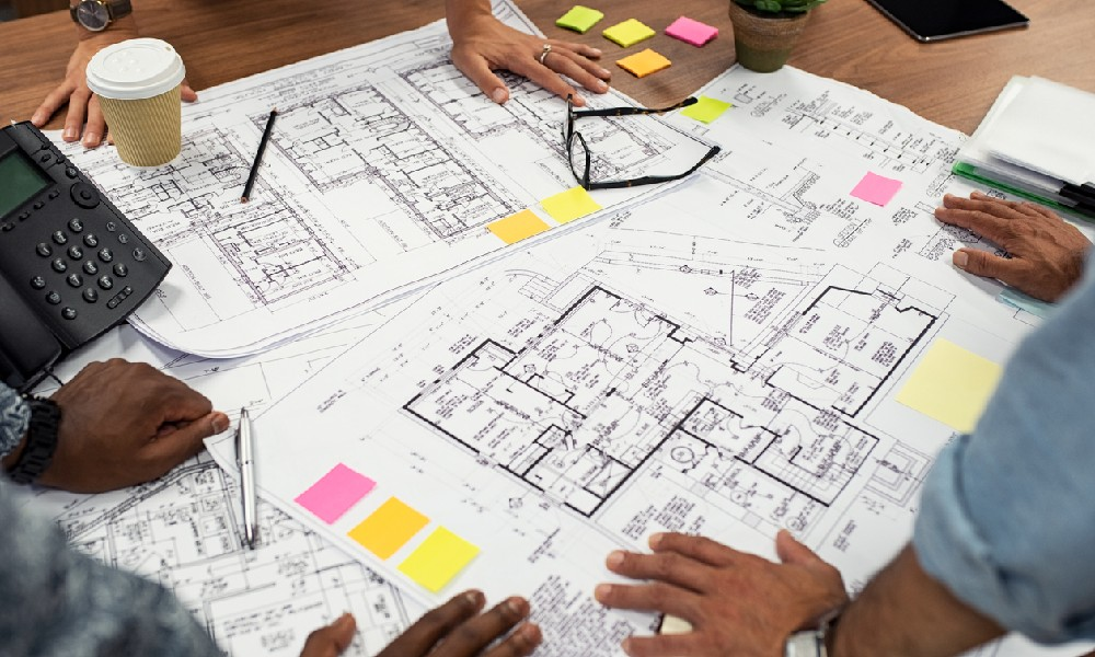 members of a design team going over some office space planning blueprints