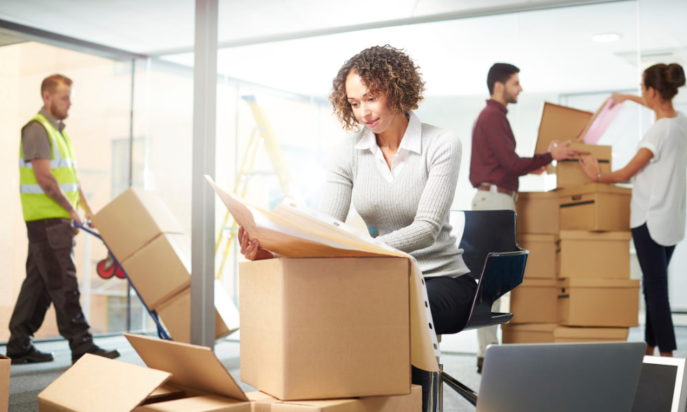 A woman checking the office moving checklist while other in the back pack up office equipment