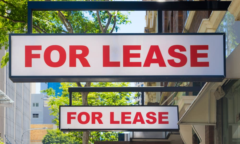 two for lease signs next to each other