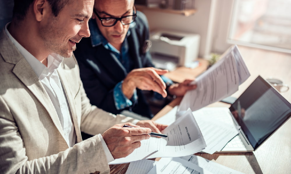 Two men put together a comparative lease analysis while looking for the ideal space for a business.