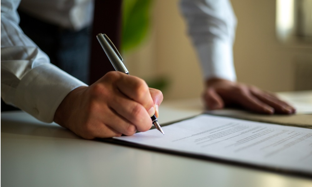 investor signing a document as he finalizes the process of buying commercial property