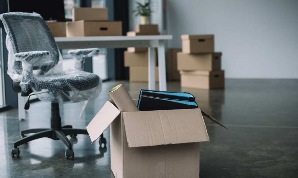 a business in the process of relocating, with supplies in boxes and chairs wrapped for the move.