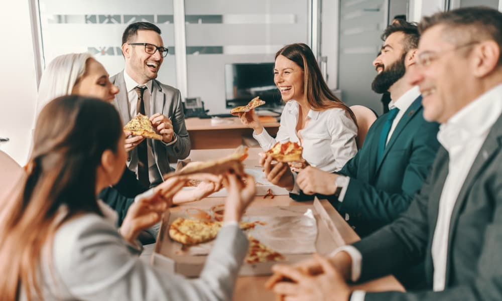 a group of employees enjoying a work-life balance in the office by gathering for pizza